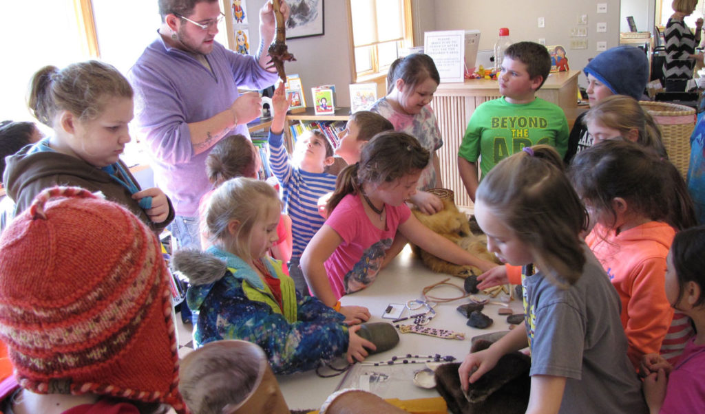 Students from the Swan's Island Elementary School examine some of the artifacts Abbe Museum educator George Neptune brought to his presentation.