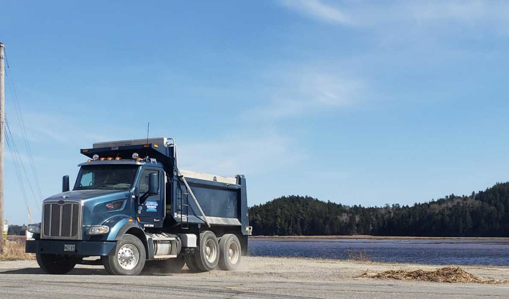 A Maine Department of Transportation dump truck pulls off of the Downeast Sunrise Trail