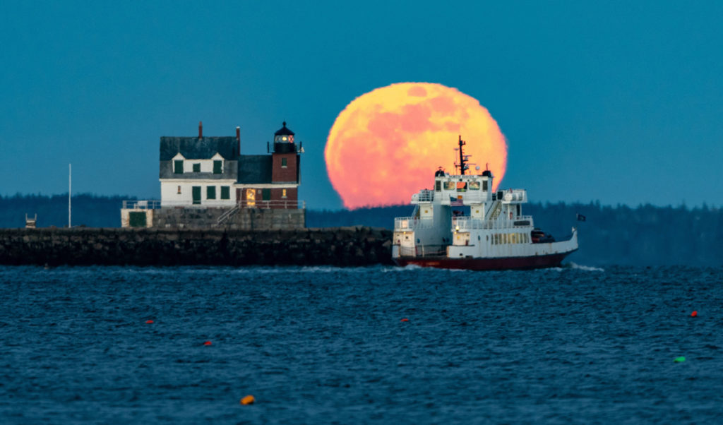 A Maine State Ferry Service boat rounds the Rockland Breakwater as a full moon rises.