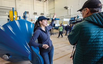 Leaning up against one of the pontoons of the RivGen Power System, ORPC ocean engineer Melozi Scott answers questions about its operation.