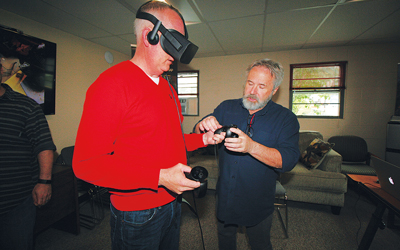 Chuck Carter, founder of Eagre Games and developer of a recently debuted game called ZED, helps First National Bank CEO Tony McKim don VR goggles and controllers.