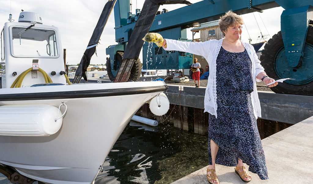 Capt. Pam Parker of the Maine Department of Environmental Protection christens Friends of Casco Bay's new pump-out boat.