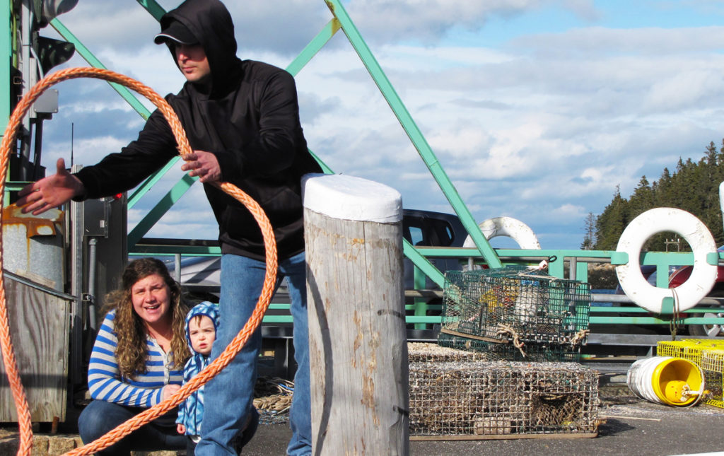 An island family helps a boat land at Frenchboro's ferry landing.