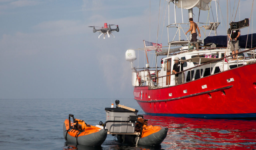 A drone hovers near a simulation of a whale exhaling.