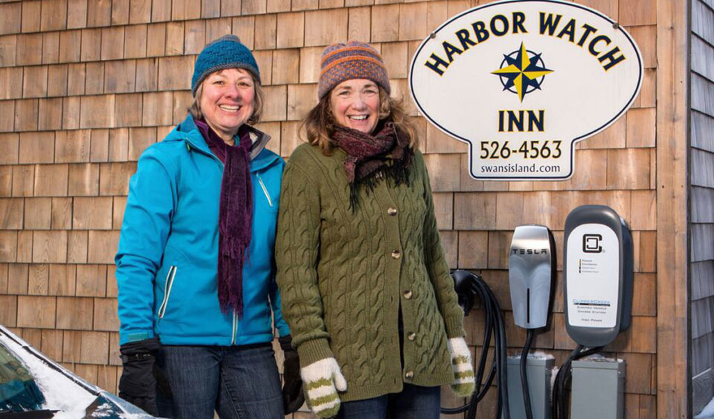Harbor Watch Inn owner Colleen Hyland (right) looks on as Janice Kenyon of Southwest Harbor uses the inn's new charging station with her all-electric 2015 Nissan Leaf.