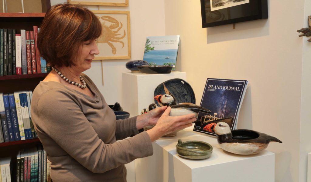 Archipelago's assistant manager Frances Holdgate shows off Richard Robertson's ceramic work.