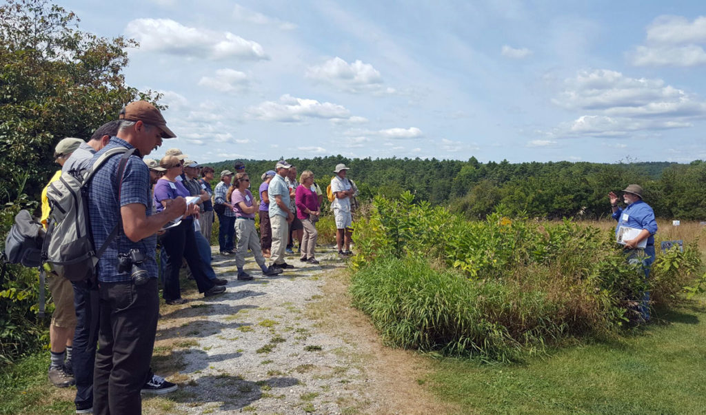 Conference attendees at Whaleback Shell Midden Historic Site in Damariscotta listen to Arthur Spiess