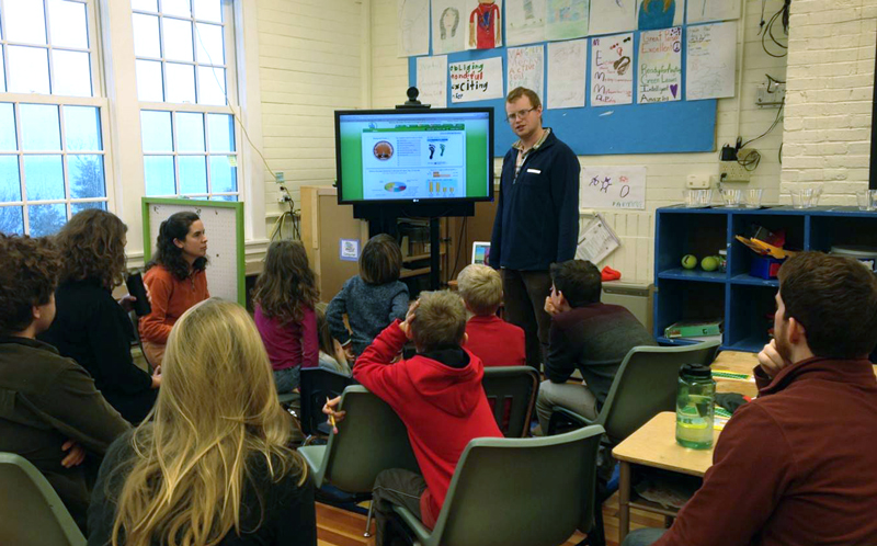 Ben Algeo explains the eMonitor to Monhegan students during Energy Day in January