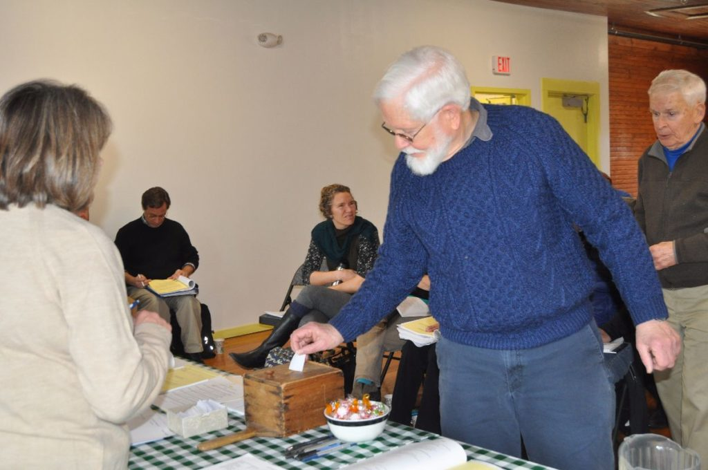 Skip Stevens votes on a warrant article at the Cranberry Isles town meeting at Longfellow School on Saturday.