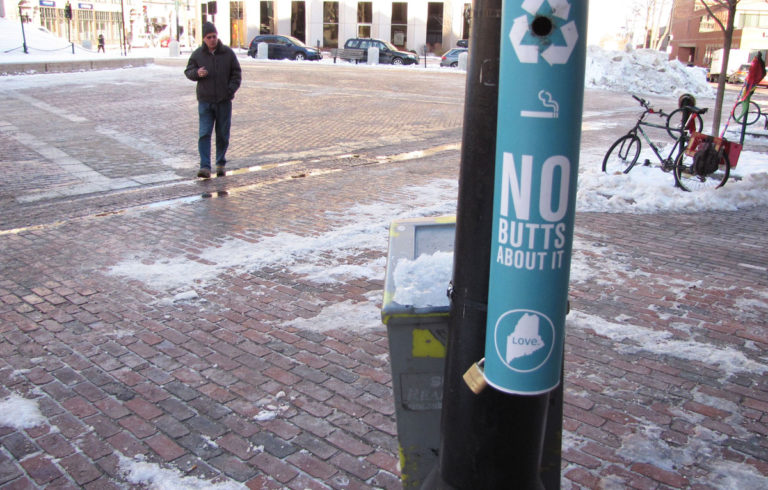 "A smoker approaches the ""Buttler"" in Monument Square."