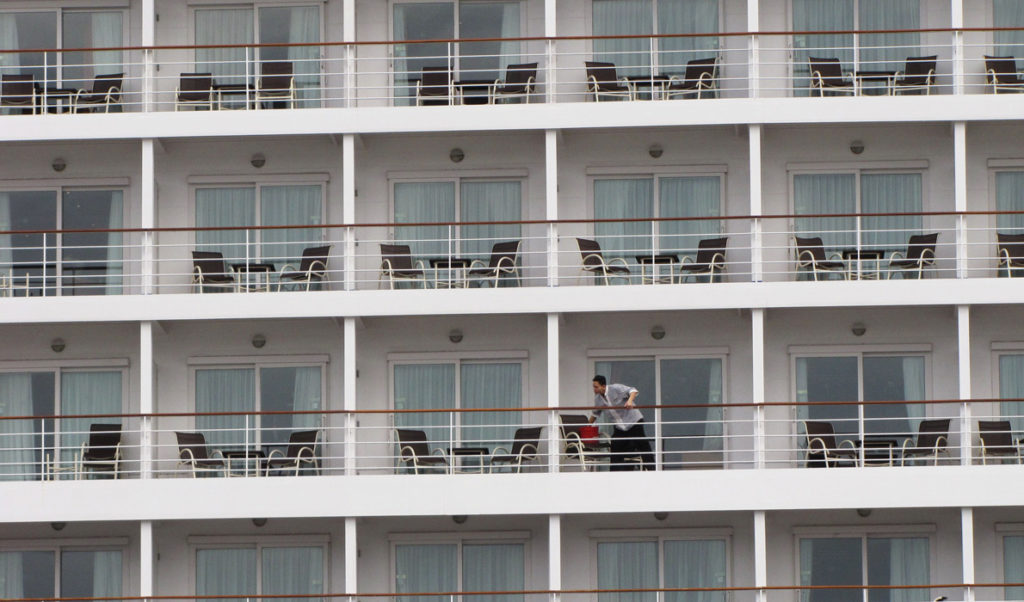 A crew member cleans balconies on a cruise ship docked at Portland's Ocean Gateway in 2014.