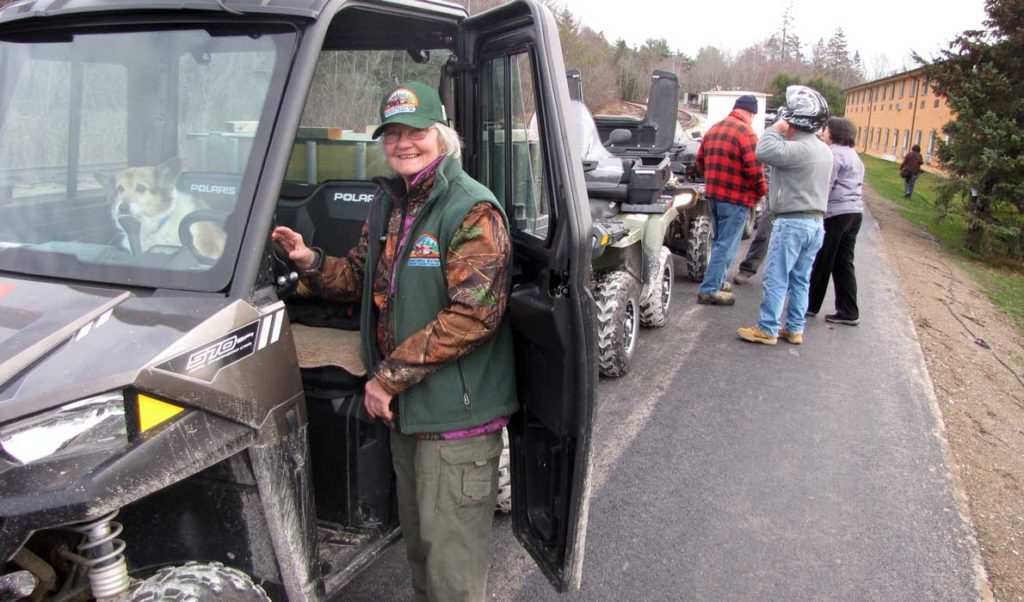 Muggsy Britts and her dog prepare to start her ATV. Britts is a member of the Acadia Area ATV club.