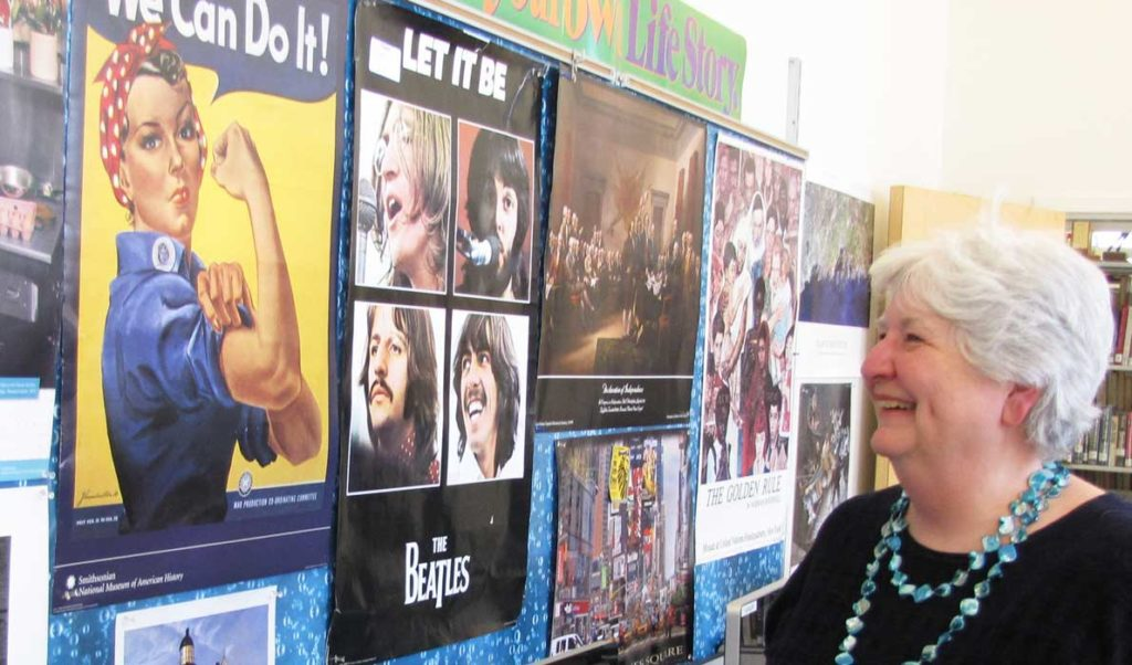 Donna Damon poses in front of a bulletin board in her classroom that reflects her life.