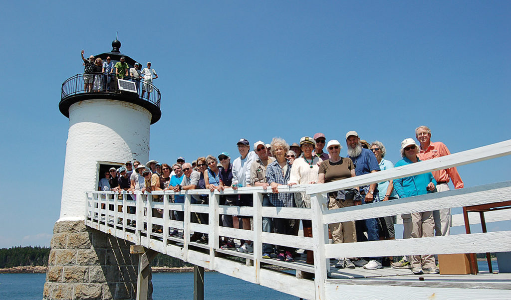 Members of the two island lighthouse committees pose on the walkway at the Isle au Haut light.