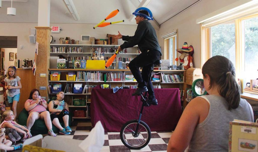 Zach Field wows the crowd as he juggles and rides a unicycle.