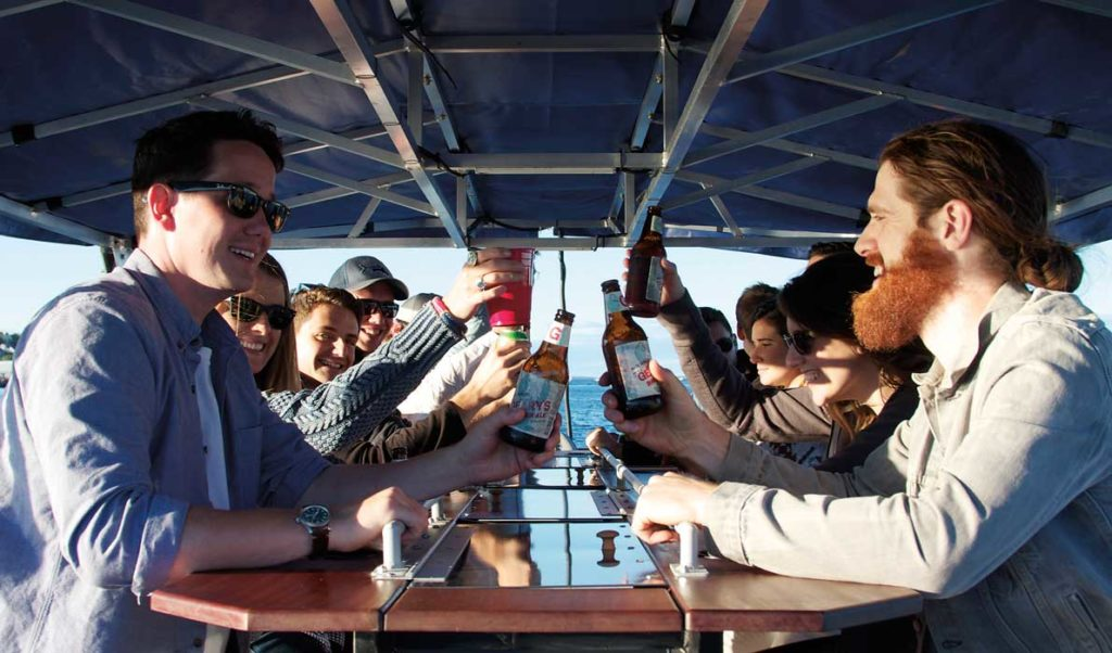 Pedalers on the foot-powered Maine Baycycle enjoy their beverages.