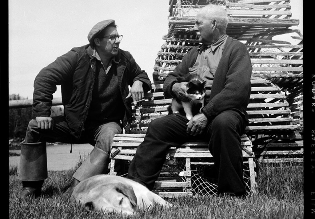 Fisherman George Curtis and retired fisherman William Leaman talk fishing (of course) outside of Leaman's fish house in Owls Head in 1957.