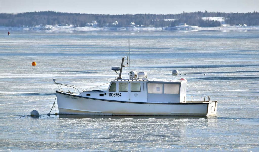 A lobster boat surrounded by ice in Lincolnville Beach.