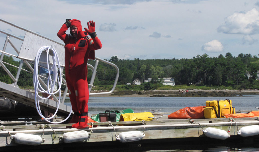 Demonstrating an immersion suit.