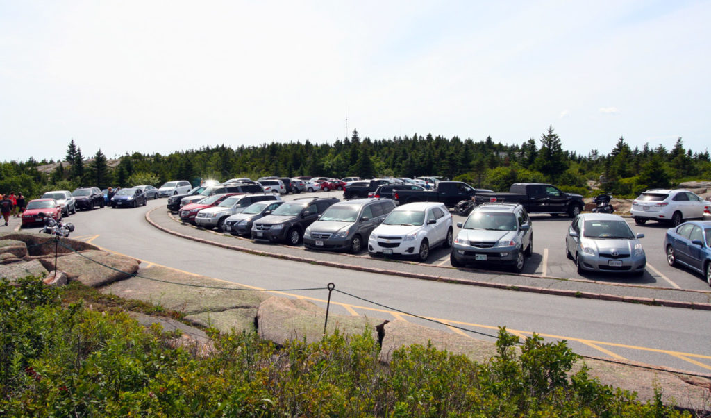 Cars fill the parking spaces at the top of Cadillac Mountain in Acadia National Park.