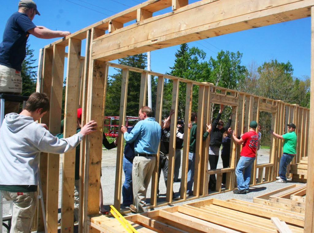 MDI High School students in a previous Habitat for Humanity class do a trial fit of their walls before the units are shipped to the house site.
