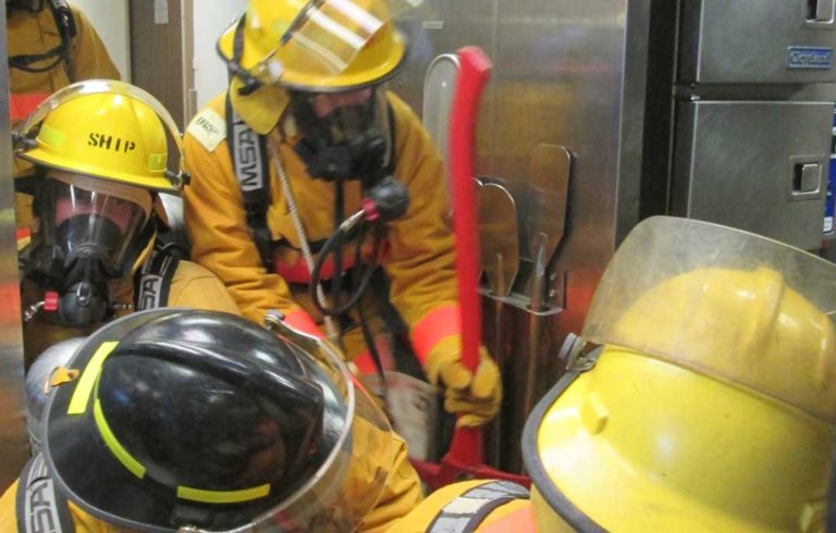 Firefighters squeeze into the galley to fight a simulated grease fire.