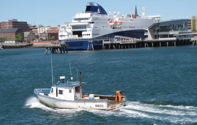 A lobster boat cruises through Portland Harbor with the Nova Star