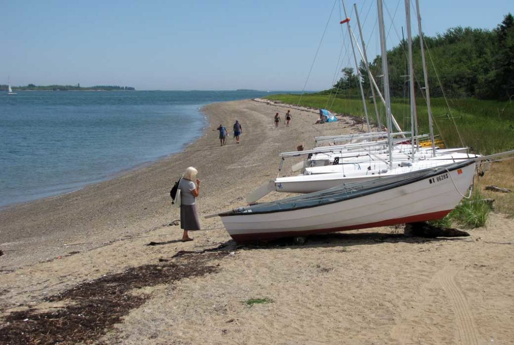 Sailboats and people on Chebeague Island shore.